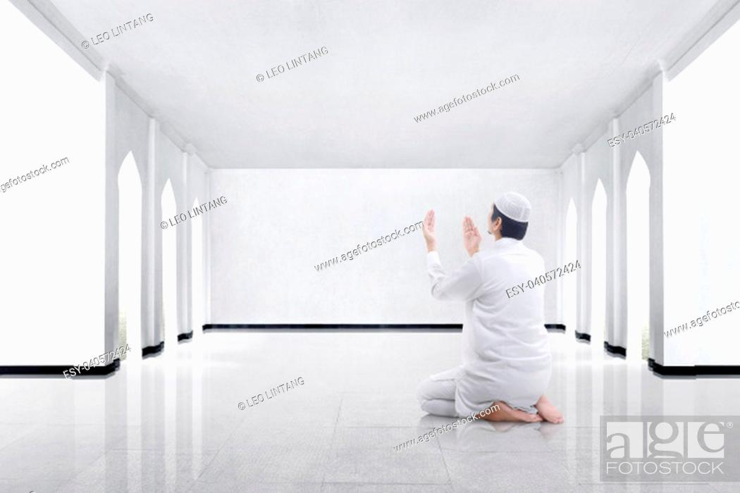 Stock Photo: Back view of asian muslim man kneeling and praying to god in the mosque.