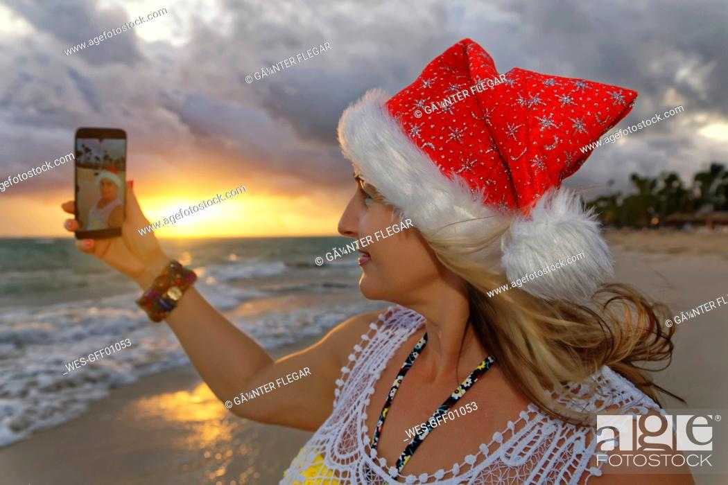 Stock Photo: Carribean, Dominican Republic, Punta Cana, woman with Christmas cap taking selfie on the beach.