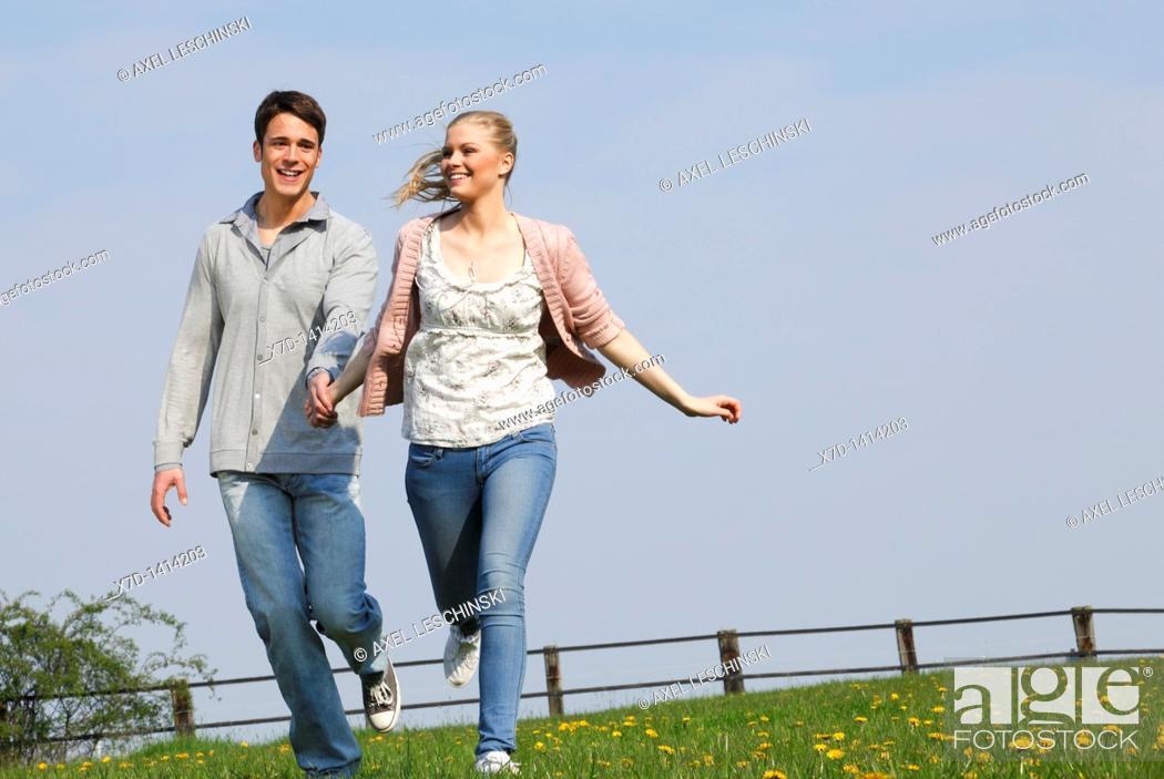 Stock Photo: Couple walking on meadow.