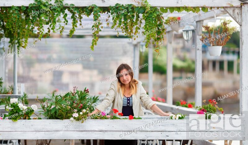 Stock Photo: Portrait of a pretty young woman in a vintage setting. Framing of the pure white paint wooden structures with ivy and flowers. Shallow depth of field.
