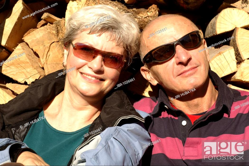 Imagen: Old-aged couple relaxing in front of a stack of wood.
