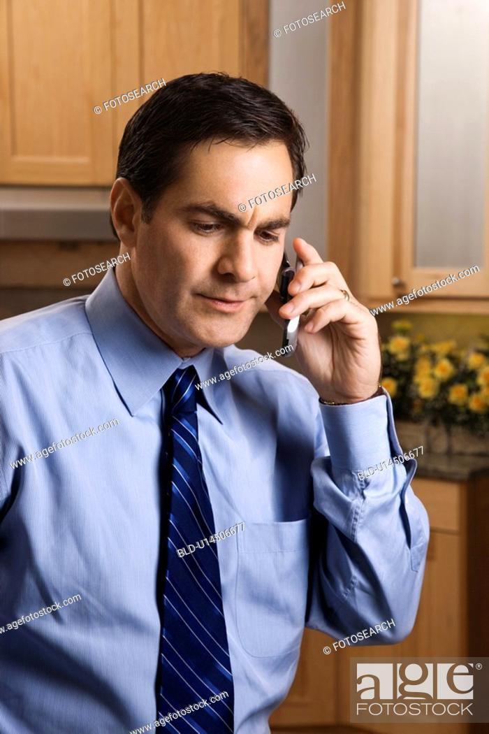 Stock Photo: Man in business apparel on a cellphone in the kitchen.