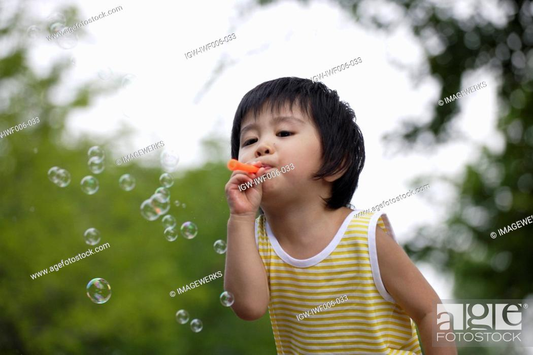 Stock Photo: A boy blowing bubbles.