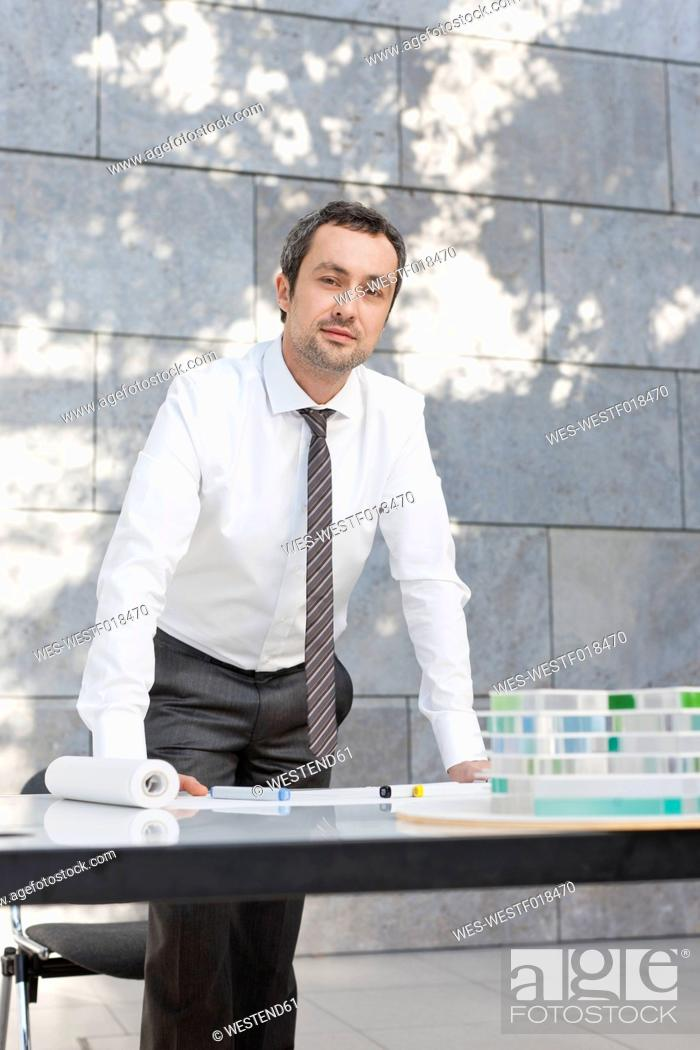 Stock Photo: Germany, Leipzig, Businessman with architectural model, portrait.
