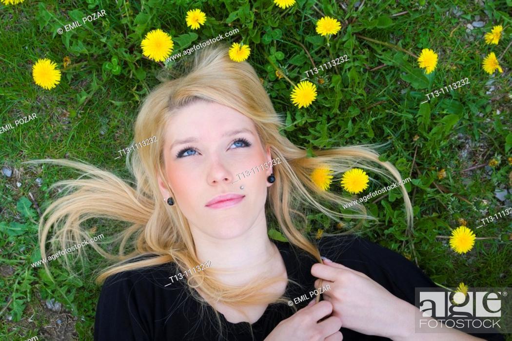 Stock Photo: Lying on Yellow dandelion flowers blonde woman portrait.