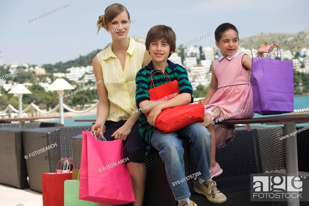 Stock Photo: Mother and two children with shopping bags.