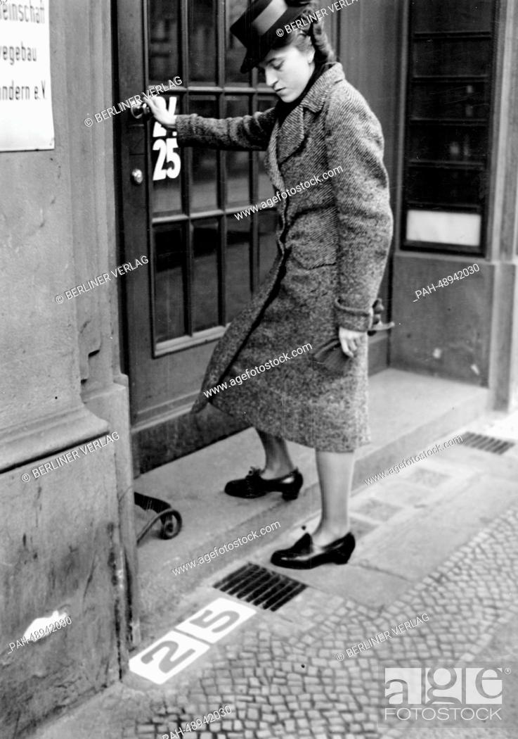 Stock Photo: The picture from a Nazi news report shows a woman walking into a building next to the newly introduced address number stones in Berlin, Germany, November 1940.