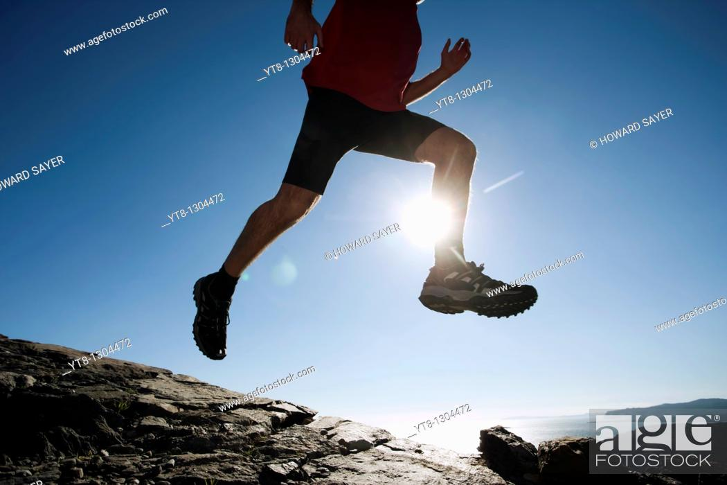 Stock Photo: Man leaping through the air whilst running.