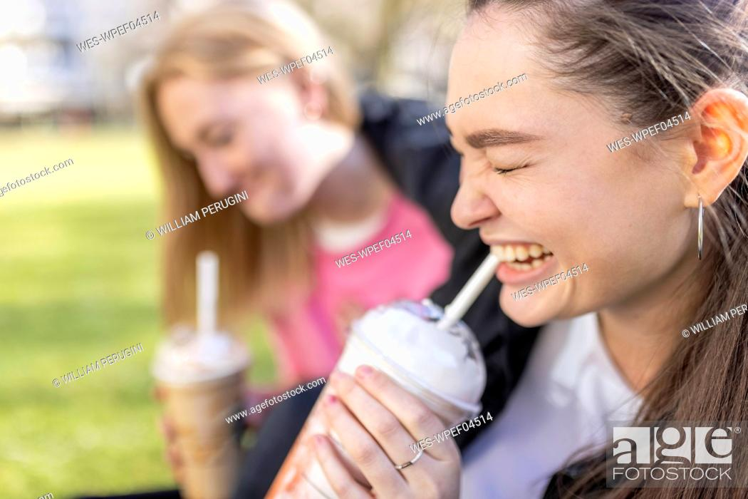 Stock Photo: Happy woman drinking milkshake with female friend in background at public park.