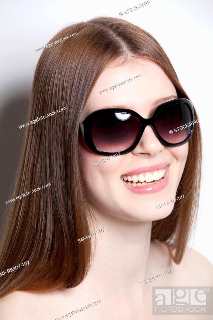 Stock Photo: Brunette young woman wearing sunglasses.