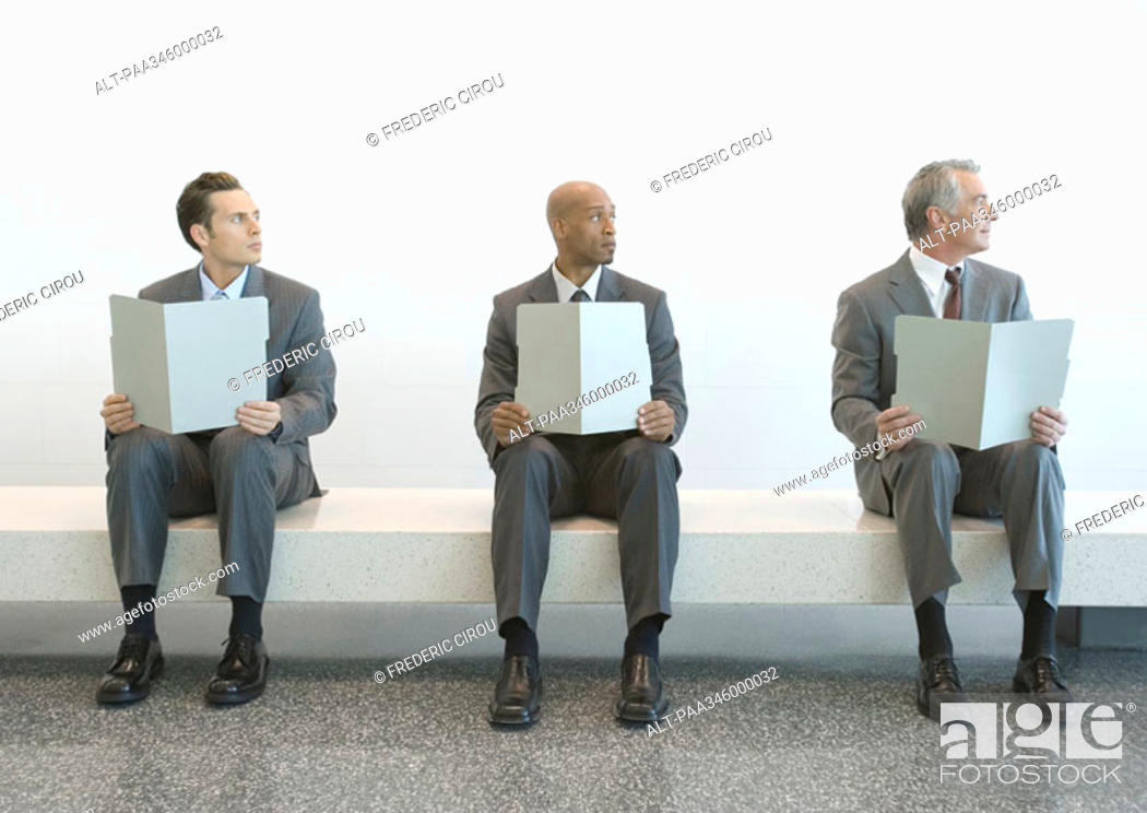 Stock Photo: Three men in suits sitting in a row, holding up files, and looking away.