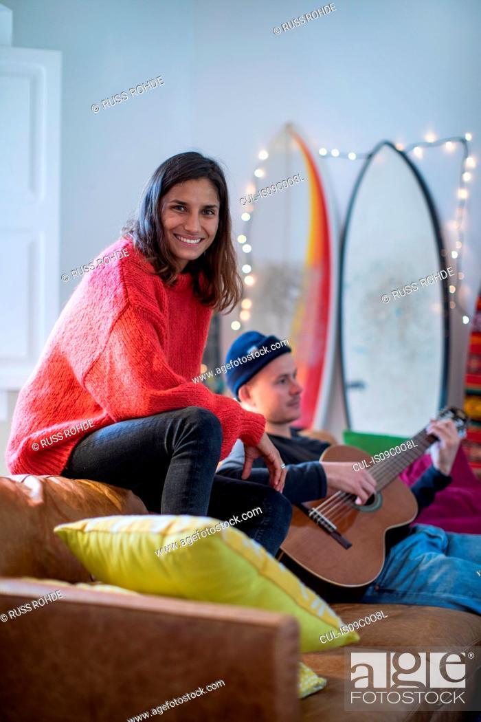 Imagen: Young woman sitting up on living room sofa with young man playing guitar.