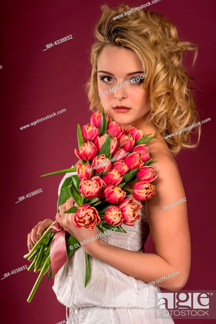 Stock Photo: Young woman posing with bouquet of flowers, tulips, fashion, lifestyle, portrait.