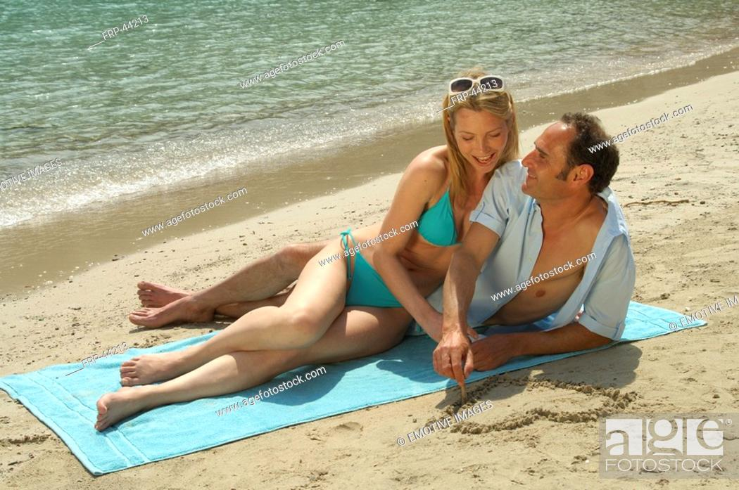 Stock Photo: Couple lying on the beach, he is painting a heart into the sand.