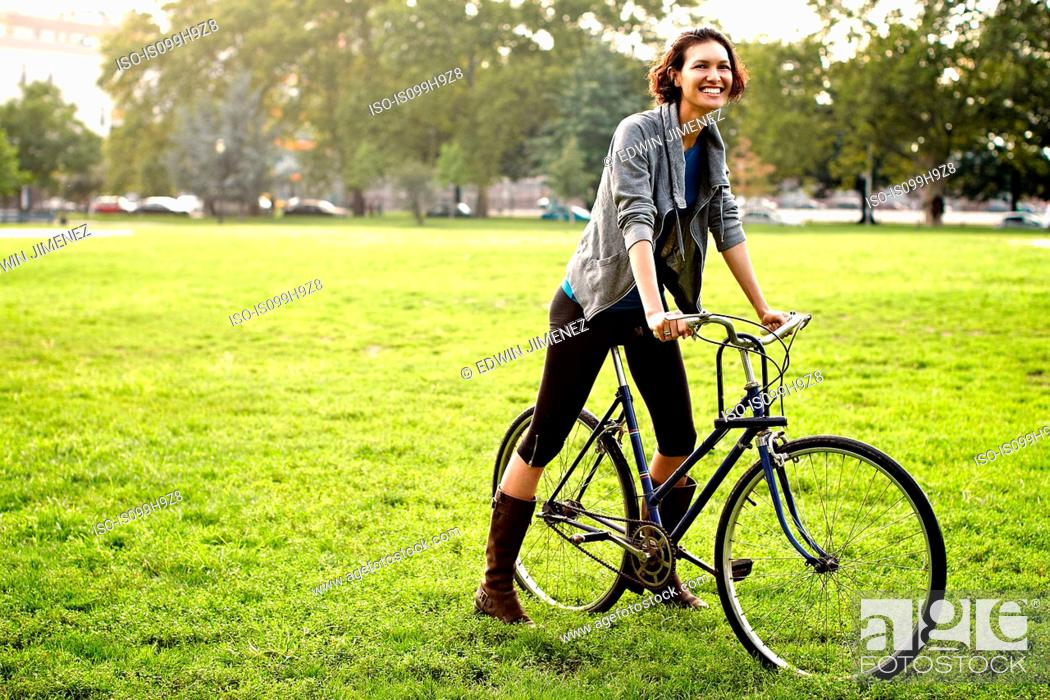 Stock Photo: Young woman on bicycle in park.