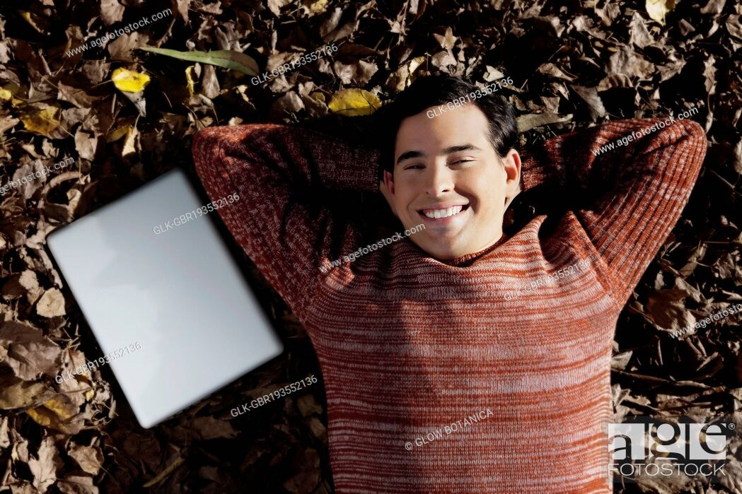 Stock Photo: Man with a laptop lying on autumnal leaves.