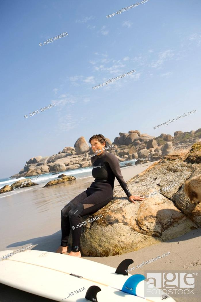 Stock Photo: Woman surfer in wetsuit with surfboard on rock on beach, smiling.