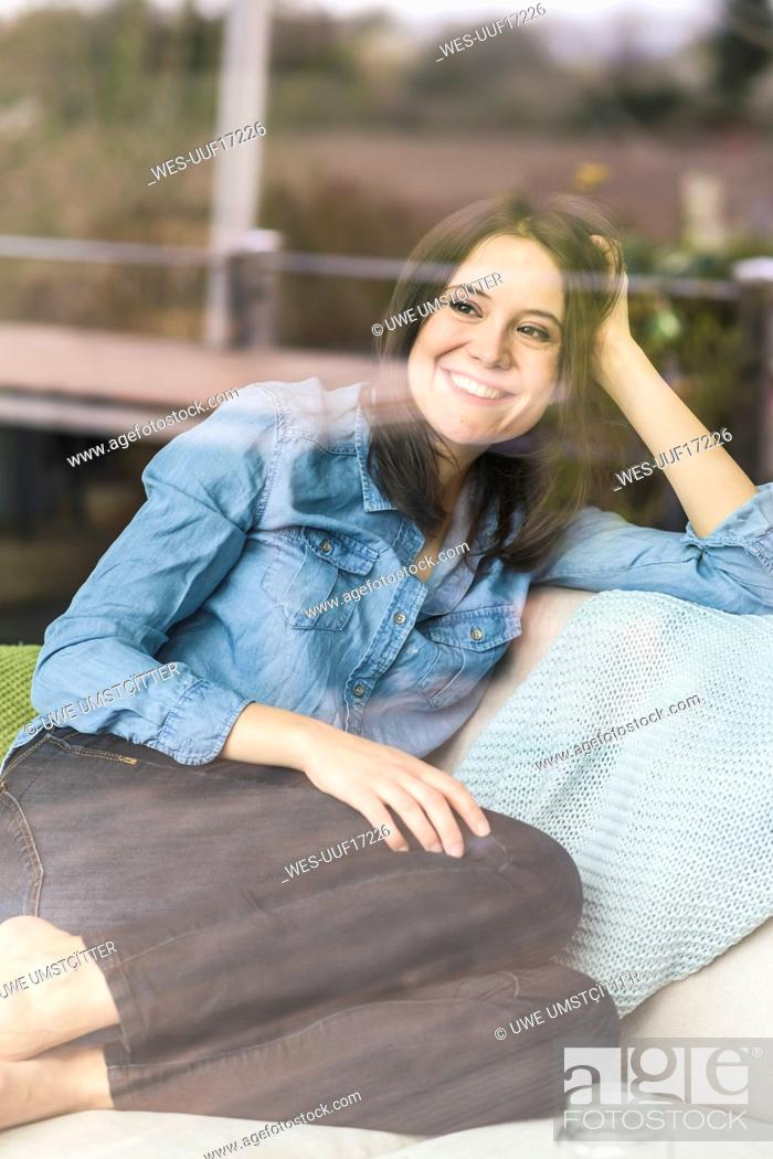 Photo de stock: Portrait of happy woman behind windowpane at home.