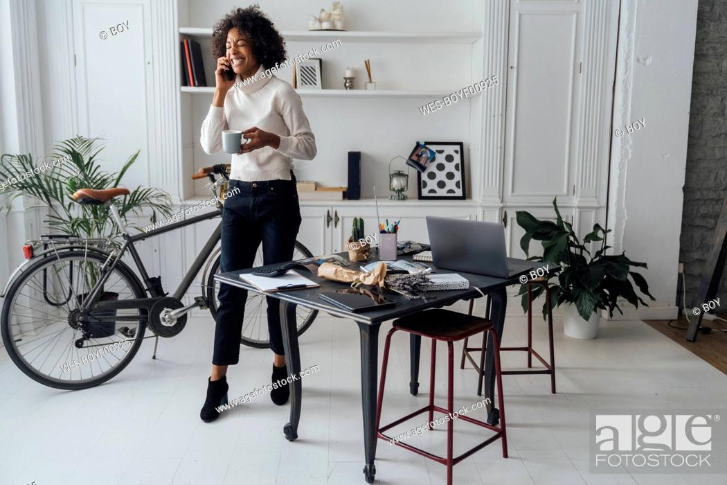 Stock Photo: Mid adult freelancer standing in her home office, drinking coffee, talking on the phone.