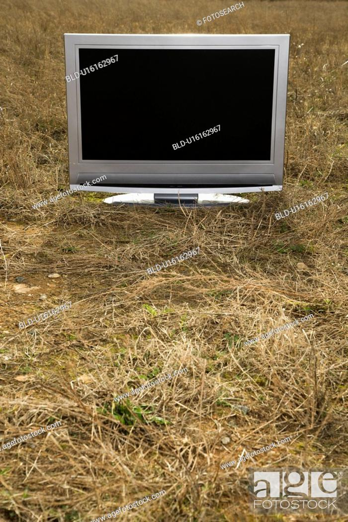 Stock Photo: Flat panel television set in grassy field.