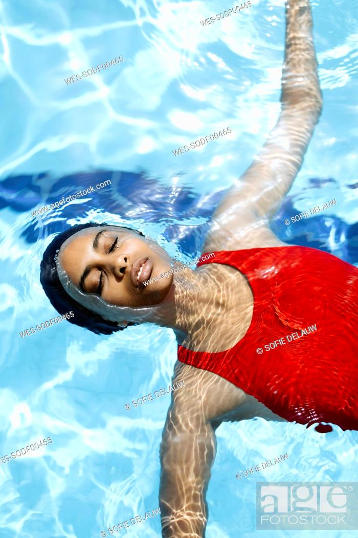 Stock Photo: Portrait of young woman with eyes closed floating on water in swimming pool.