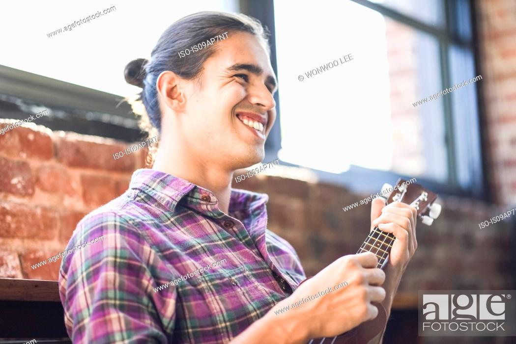 Stock Photo: Young man playing ukulele.