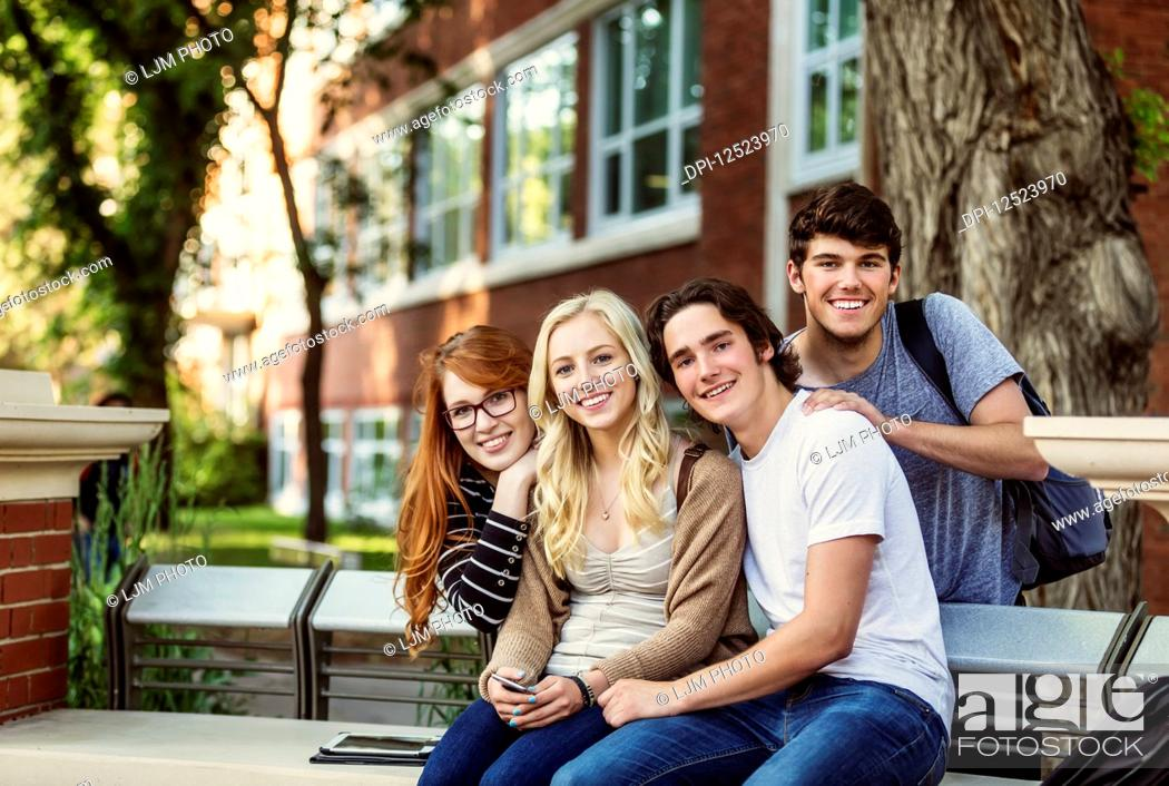 Photo de stock: Portrait of a group of four friends sitting on a bench on a university campus; Edmonton, Alberta, Canada.