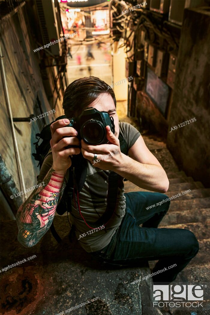 Stock Photo: A male traveler taking a photograph with his camera in a narrow street; Xiamen, Fujian, China.