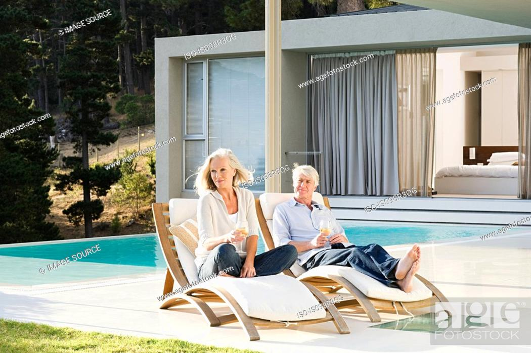 Stock Photo: Middle aged couple relaxing on deck chairs by the pool.
