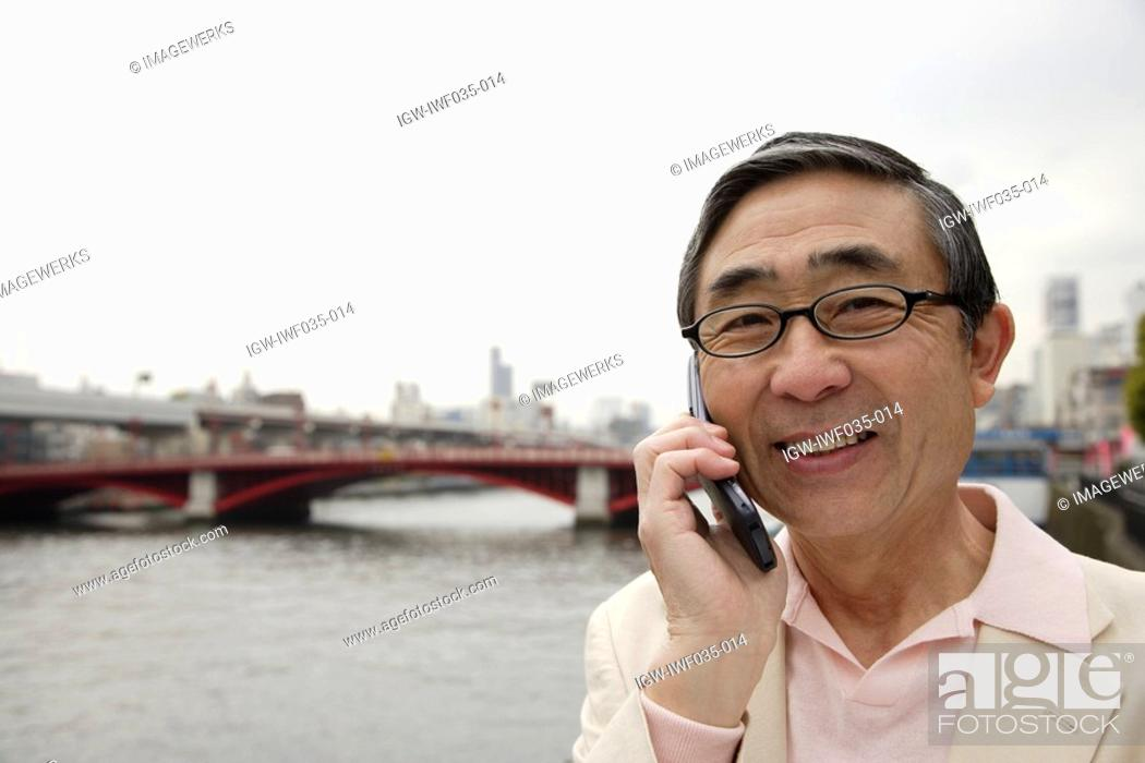 Stock Photo: Portrait of a smiling senior man using mobile phone.