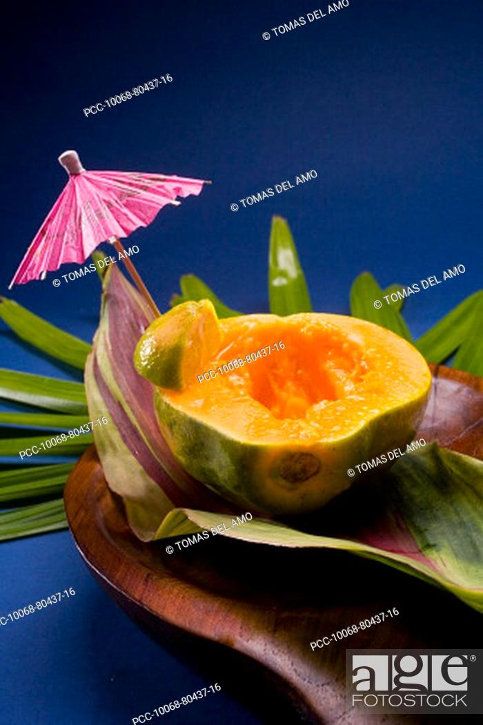 Stock Photo: Studio shot of half of a papaya, seeds removed, with cocktail umbrella.