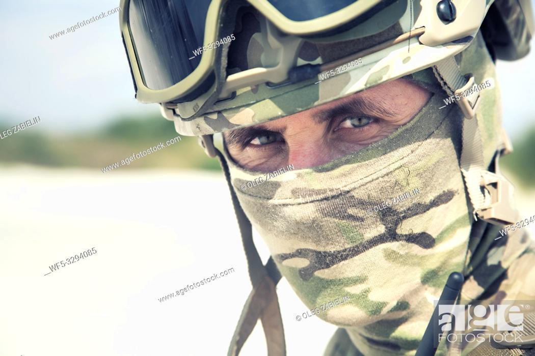 Stock Photo: Close up, cropped portrait of airsoft, strikeball war games player, military or historical reenactment participant in tactical helmet replica.