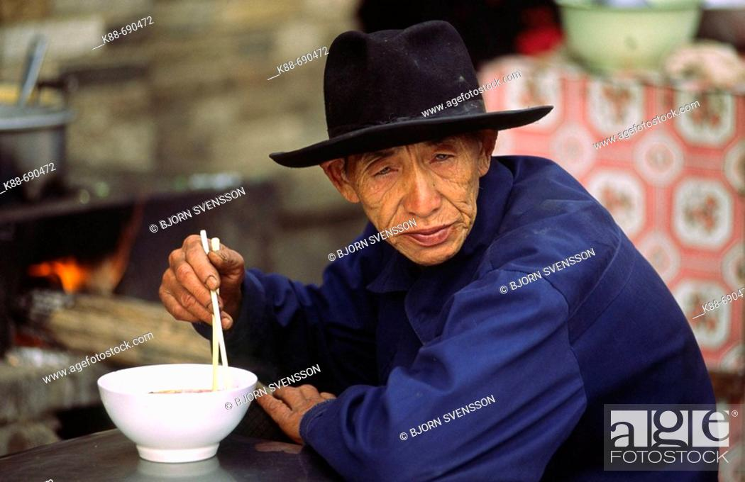 Stock Photo: Old man eating noodle soup, Xichuangbanna, Yunnan, China.