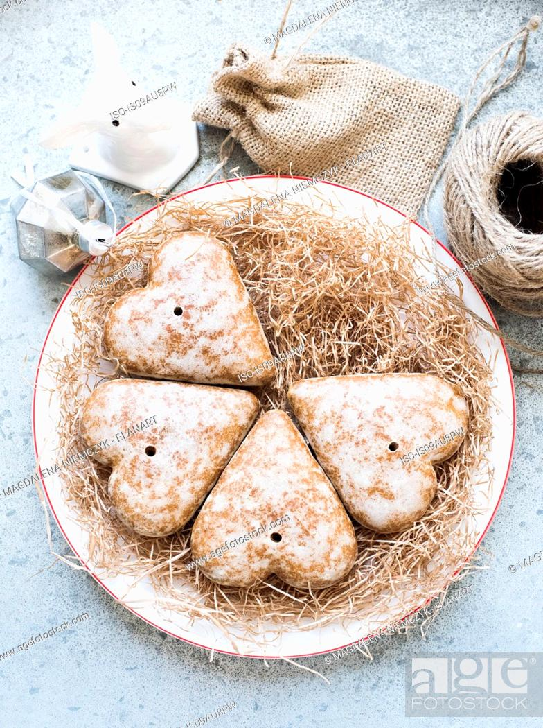 Stock Photo: Overhead view of heart shaped gingerbread biscuits on straw covered plate.