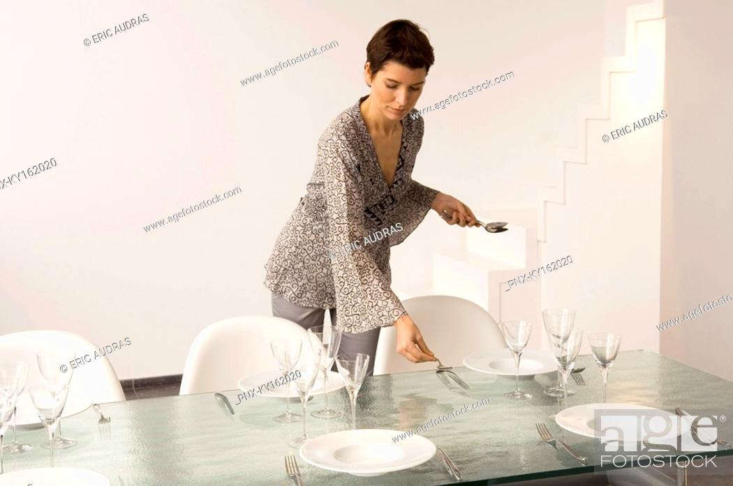 Stock Photo: Mid adult woman setting a dining table.