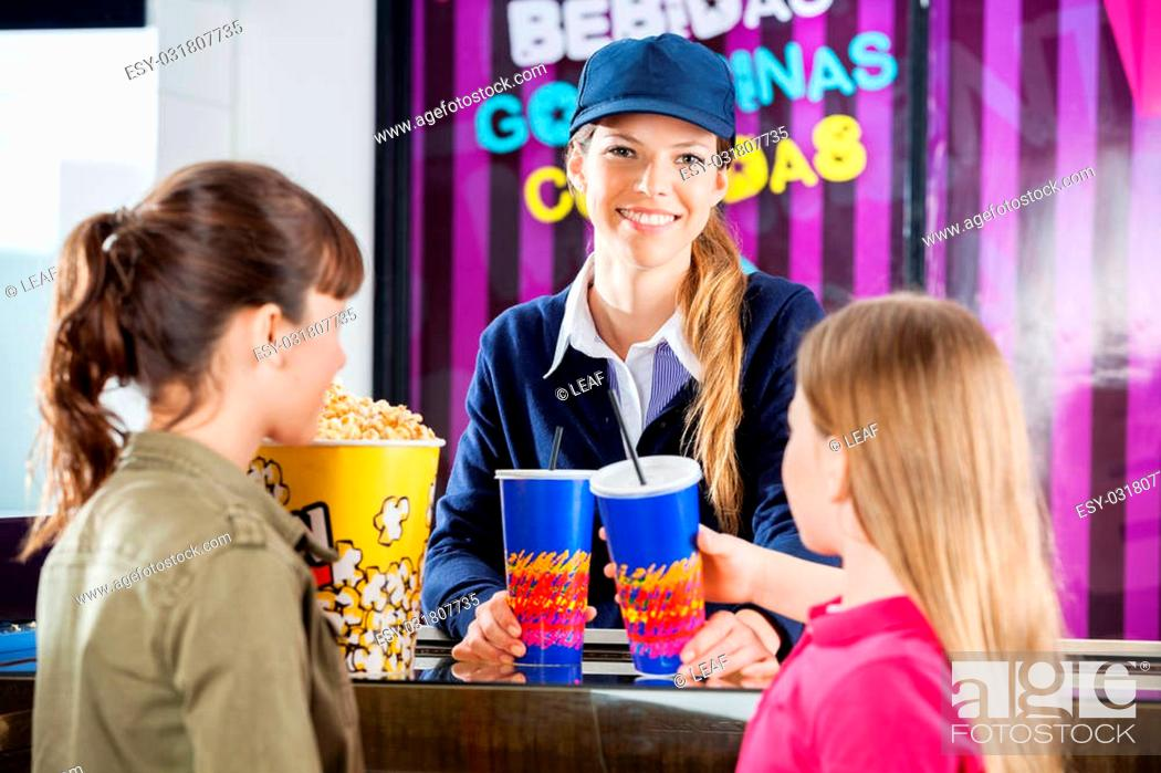 Stock Photo: Portrait of happy female worker selling snacks to girls at cinema concession stand.