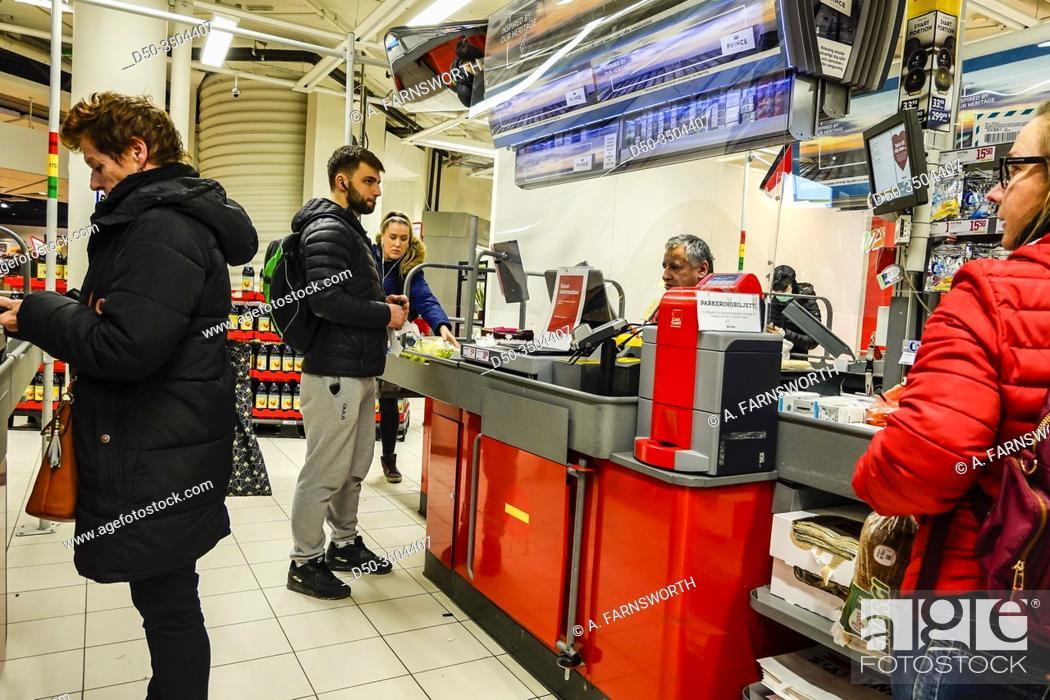 Imagen: Stockholm, Sweden April 1, 2020 Shoppers inside a supermarket in Liljeholmen stand behind plexiglas protection at the cashier.