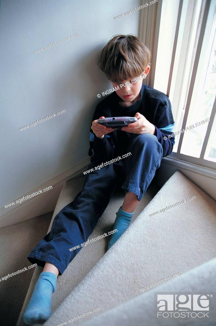 Stock Photo: kid playing video game on the staircase.
