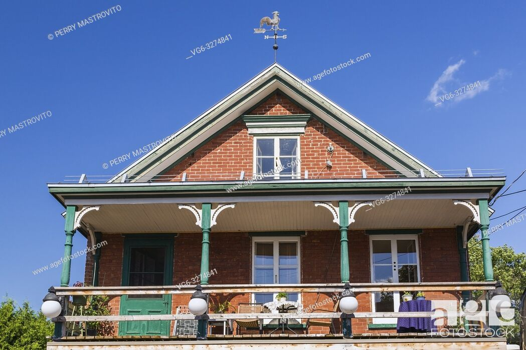 Stock Photo: Second story balcony of an old 1900s red brick cottage style house with white and green trim plus decorated wooden posts, Quebec, Canada.
