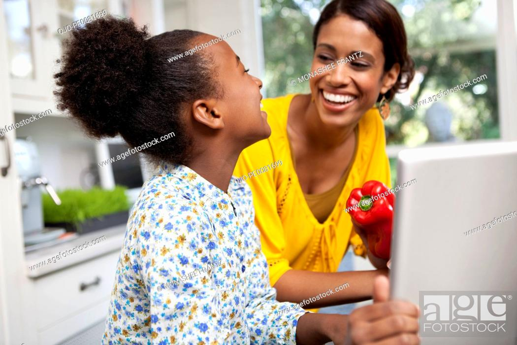 Stock Photo: Mother and daughter laughing in kitchen.