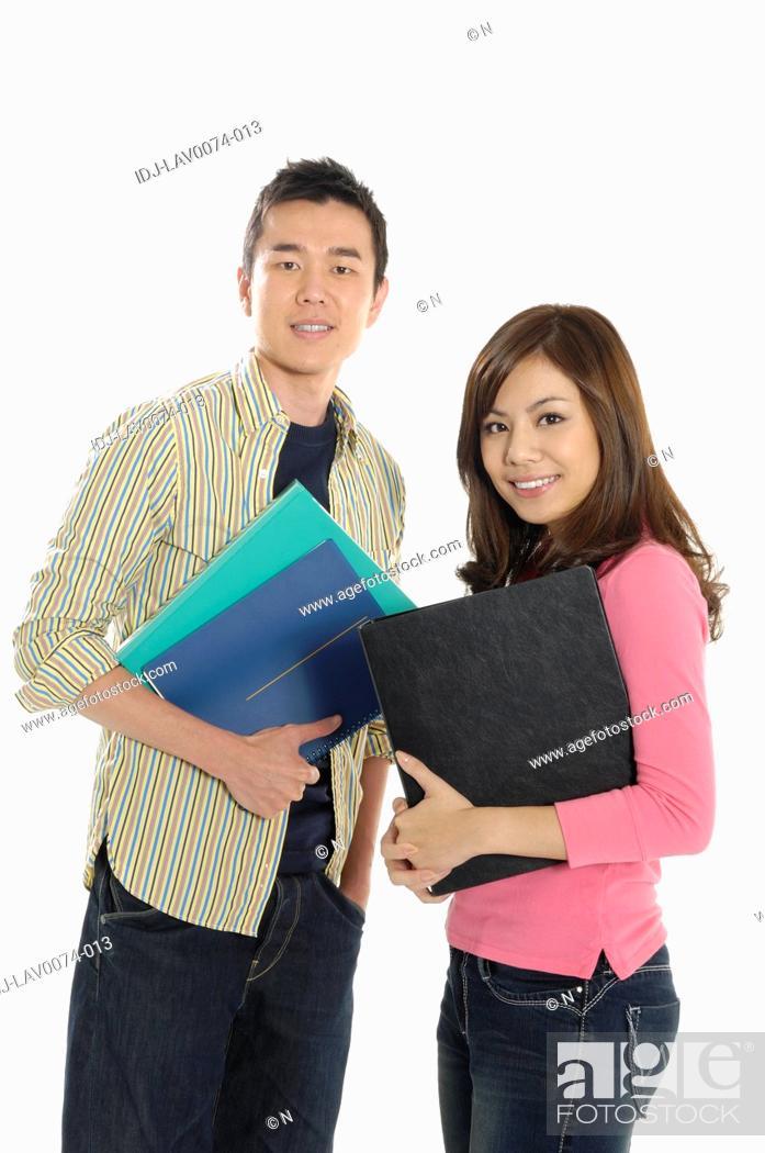 Stock Photo: University students holding books and smiling.