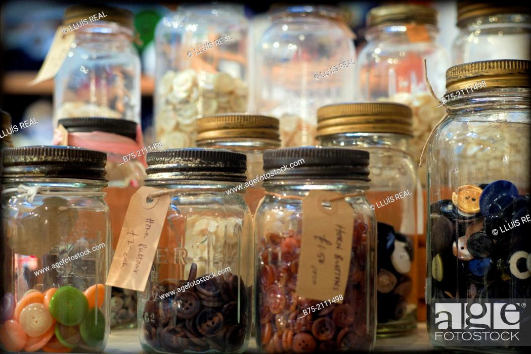 Stock Photo: A lot of buttons in glass jars with a description and a price in a warehouse, London, England, UK. Europe.