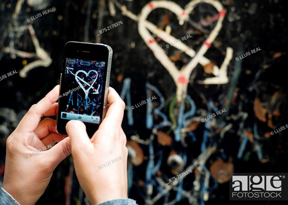 Stock Photo: Heart with arrow painted on a wall and close-up of female hands with a phone making a photo in the Medina of Fez, Morocco, Africa.