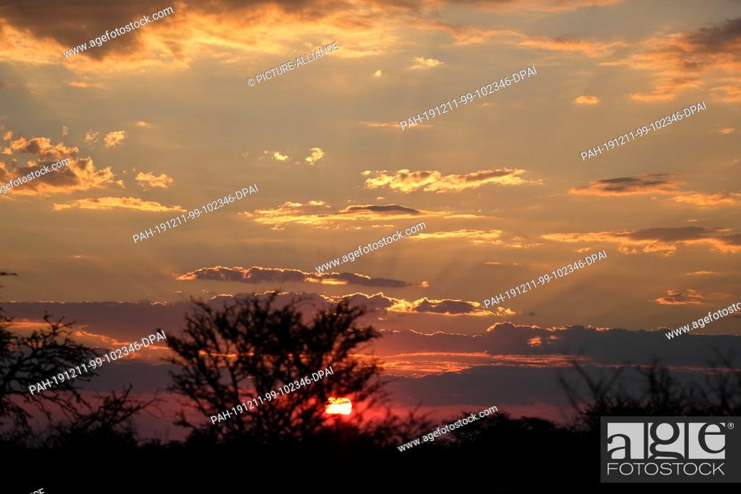 Stock Photo: 28 November 2019, Namibia, Etosha-Nationalpark: The sun sets in Etosha National Park. Photo: Oliver Berg/dpa. - Etosha-Nationalpark/Namibia.
