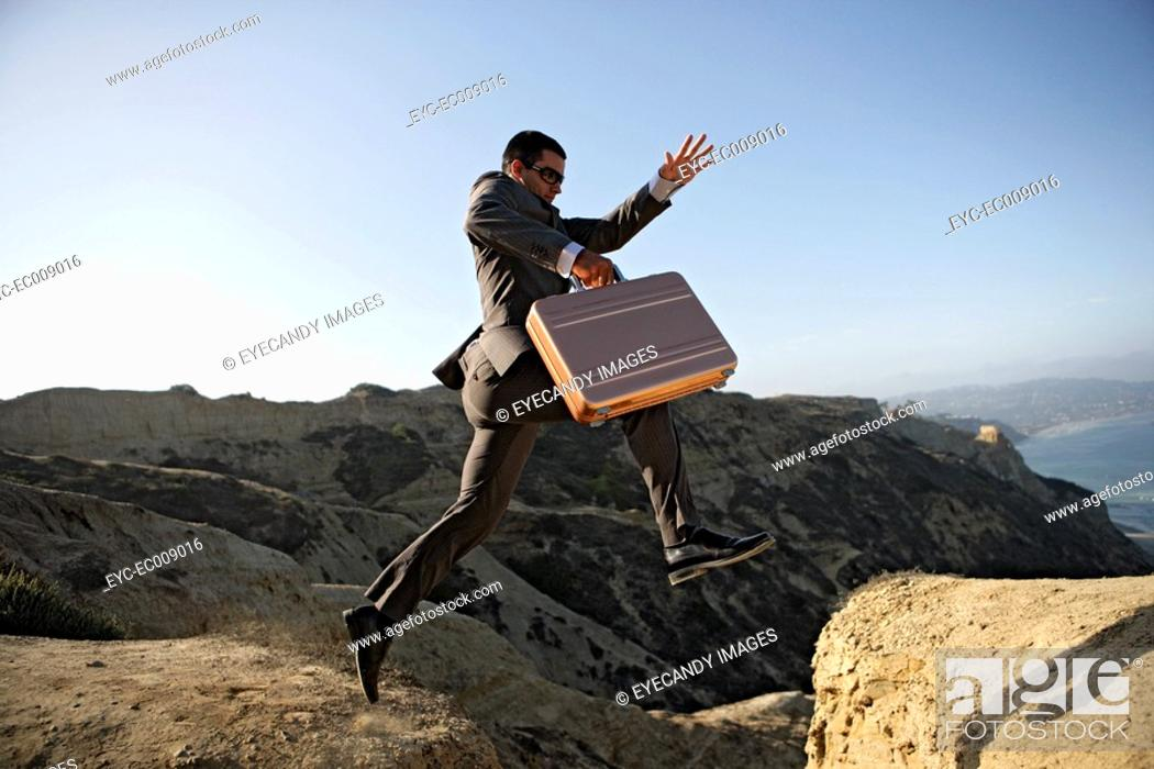 Stock Photo: Business man jumping over a cliff holding briefcase.