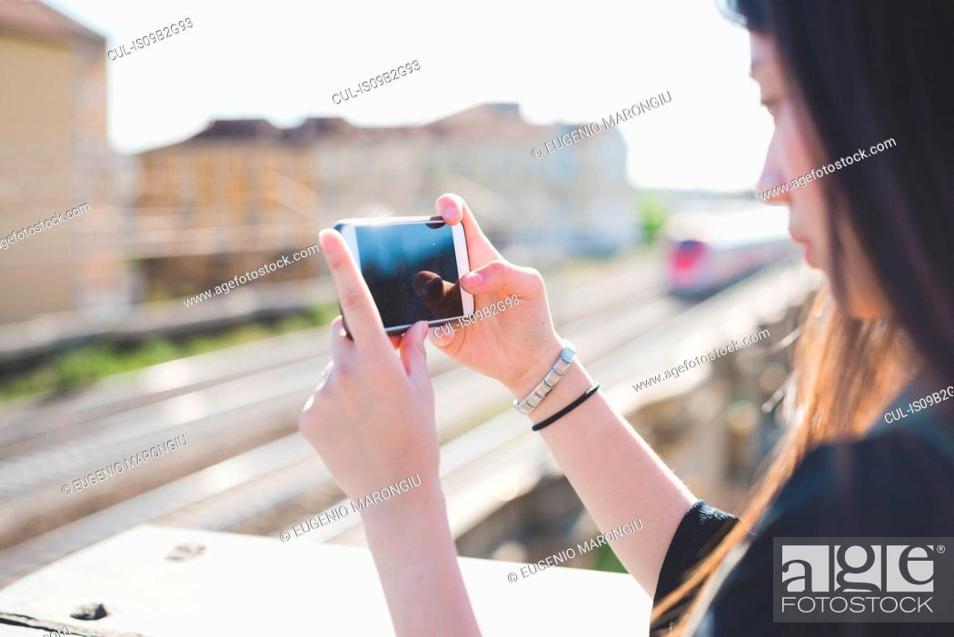 Stock Photo: Young woman on city roof terrace looking at smartphone.
