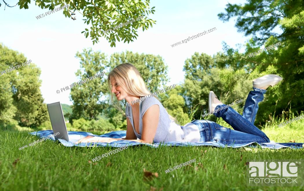 Stock Photo: Germany, Cologne, Young woman using laptop in meadow.