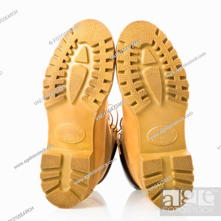 Stock Photo: Pair of tan construction boots with sole facing viewer.