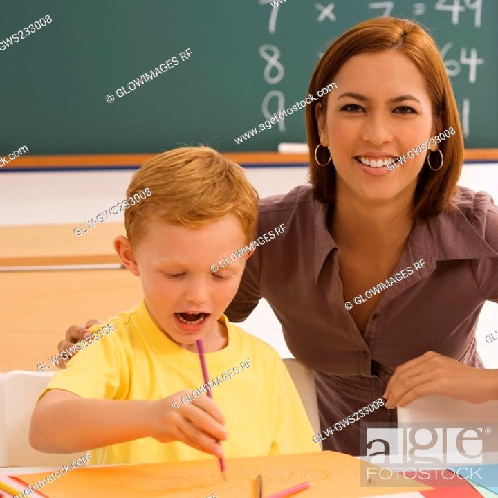 Stock Photo: Female teacher helping her student in drawing.