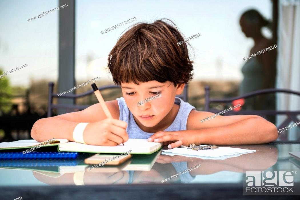 Stock Photo: Boy at table writing in workbook.